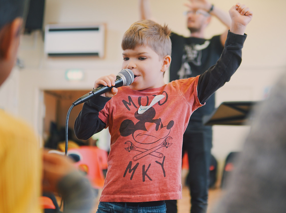 young boy singing to group