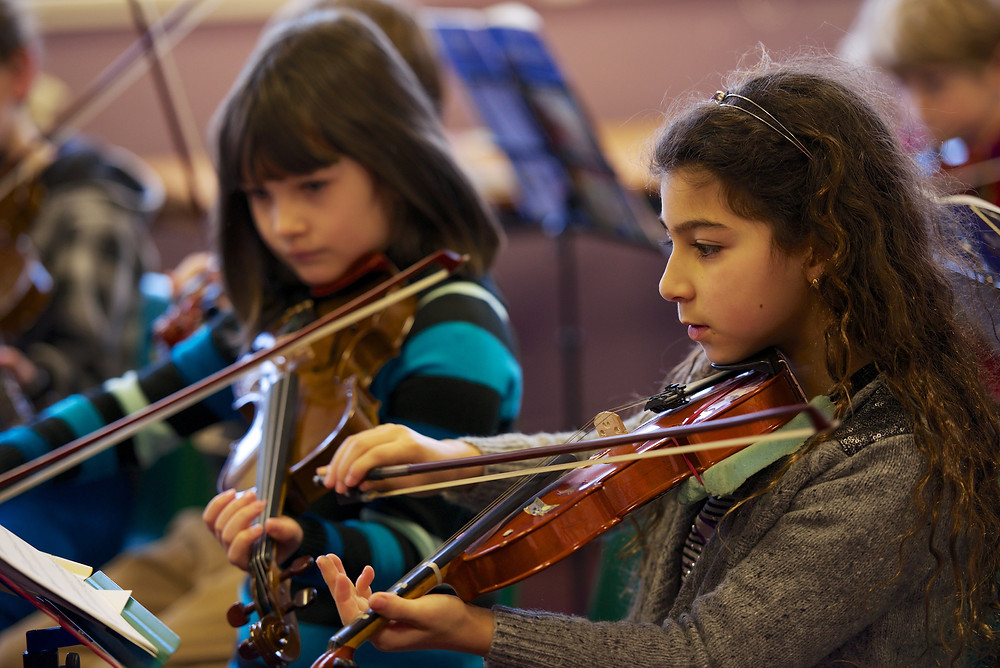 Primary aged children learning to play violin