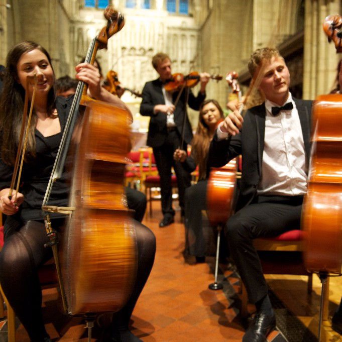 Young people spinning cellos as they play
