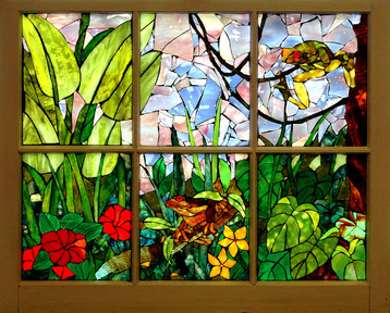 A Mosaic Window picturing a garden with flowers and a frog