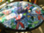 A glass mosaic table top wtih dragonflies