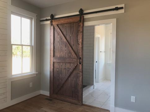 Barn door entrance to master bathroom