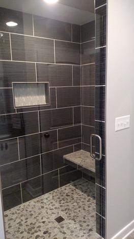 Tiled master shower with framless shower door