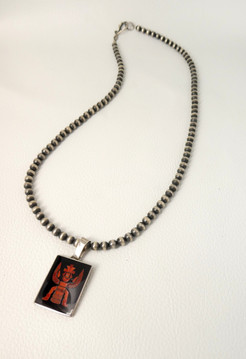 Jet and coral inlay set in silver, pendant depicting the 'Knifewing' figure