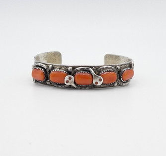Vintage Navajo silver stamped and coral row cuff with two snakes coiling by Effie Calavaza