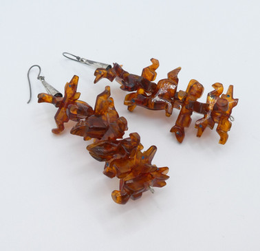 Superb fetish earrings carved in amber with silver.