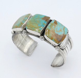 Vintage three large green square cut turquoise stones set on a silver detailed cuff.