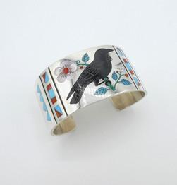 Superb fine inlay contemporary Zuni cuff depicting a black bird with floral design