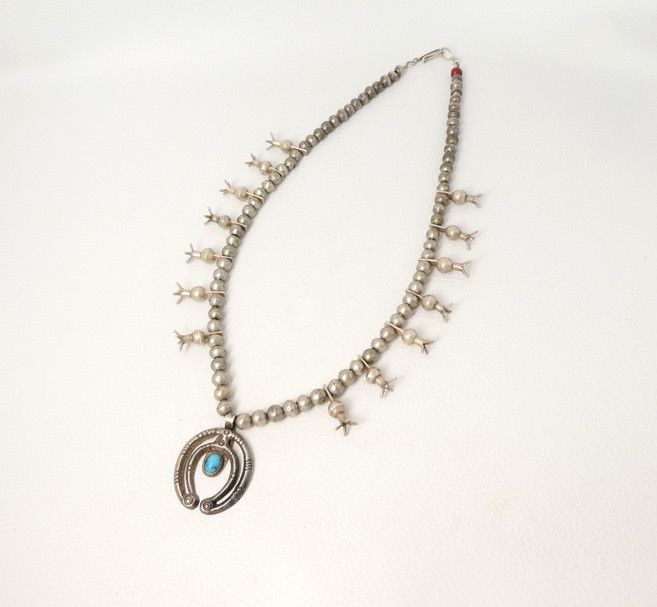 Early Navajo silver squash blossom necklace with a singular 'white heart' red trade bead and completed with a double crescent Naja with turquoise.