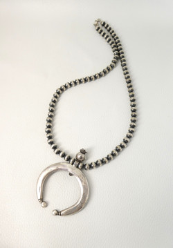 Large silver naja pendant by Dyaami Lewis on contemporary silver beads