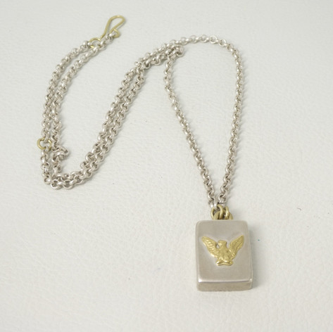 N11. Sterling and 18ct eagle charm with yellow lip mussel.