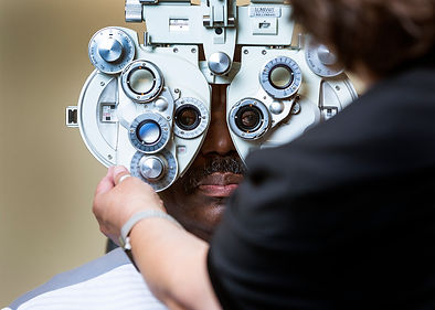An image of an optometrist placing a phoroptor in front of a patient.
