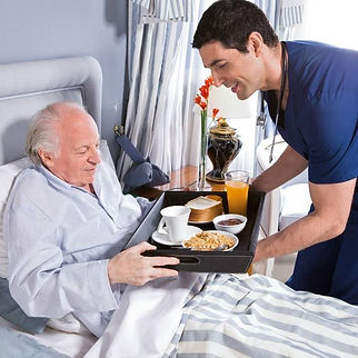 Caregiver assistance, feeding a man in bed