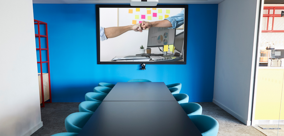 Board room with projector showing a computer desk and two hands fistbumping in the air above it.