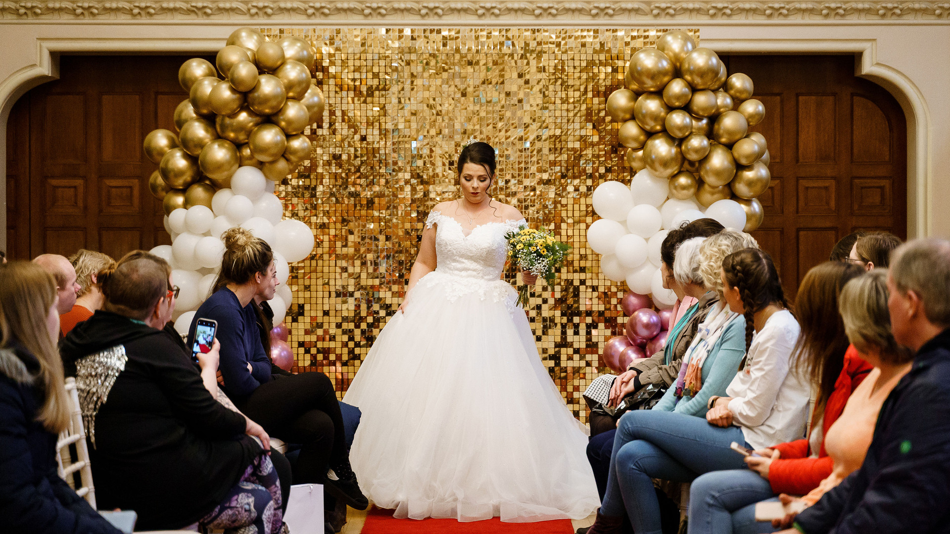 spiral events wedding fayre in winchester.  Bridal model on catwalk, wearing a Olivia George Home of The Perfect One dress, carrying flowers from The Blooming Workshop, hair by Alida K, make up by Glitter Junkie, glitter backdrop by Blooming Beautiful Backdrops, photo by Katherine and Her Camera