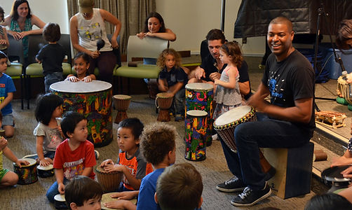 African drum musicians teach a group of children to play drums