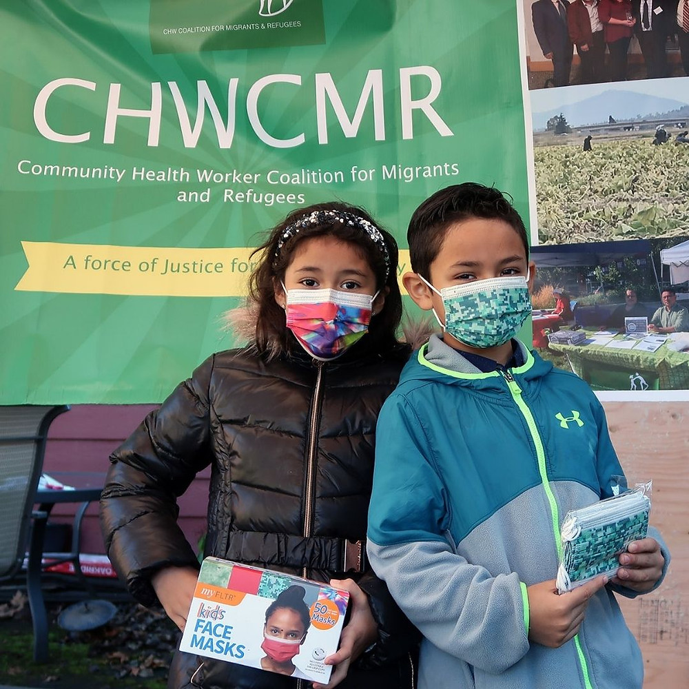 Children standing in front of green CHWCMR organization banner