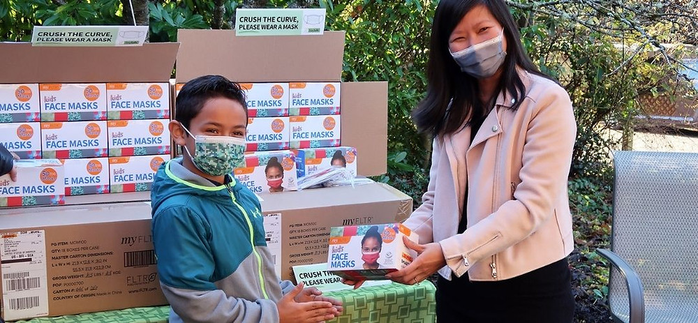Millions of Masks for Children co-founder Trang Le gives box of masks to child