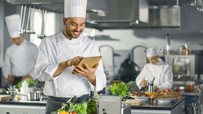 Photographie d'un chef en cuisine tenant une tablette tactile dans ses mains.