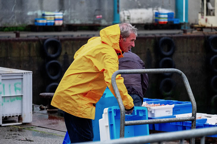 Photographie d'un pêcheur qui débarque la pêche du jour à la criée
