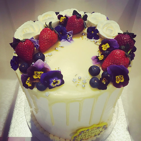 Tall cake with flowers and strawberries