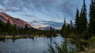 An image of Canmore's lake with surrounding trees during the evening