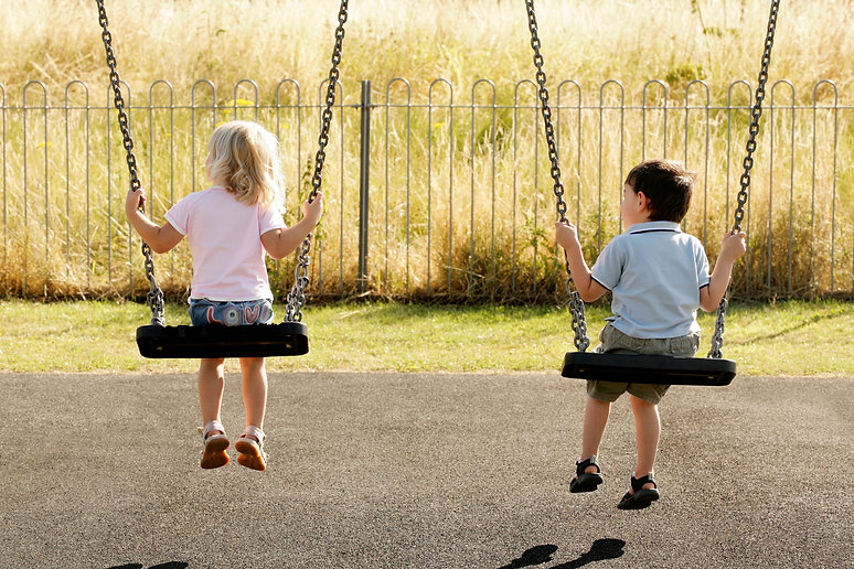 two children sitting on the swings