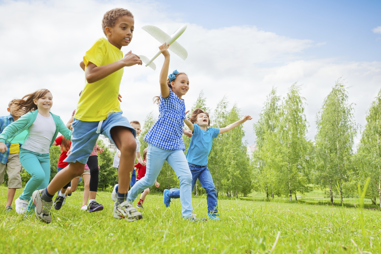 kids running in park - wellness consortium day camp