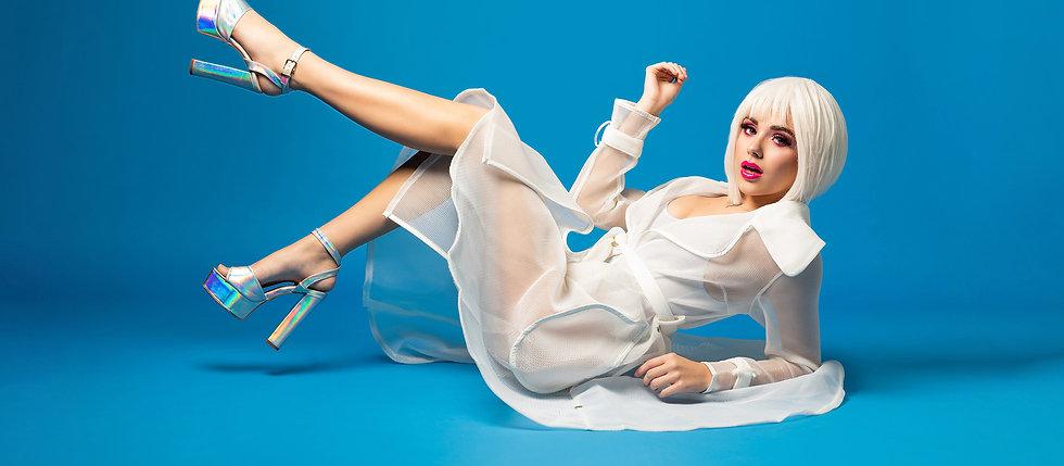 TTMO Elite Team Model Bella Fenoglio with a white wig on a blue background