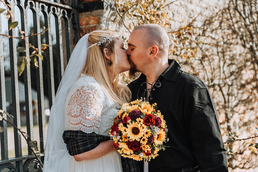 A bride an groom kiss in Gordon Castle Walled Garden, she holds a bouquet of roses and sunflowers