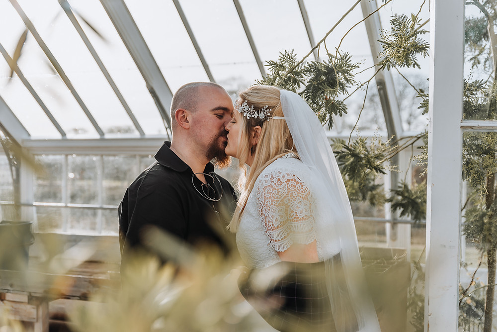 A just married coupe kiss in a greenhouse in the walled garden, fochabers