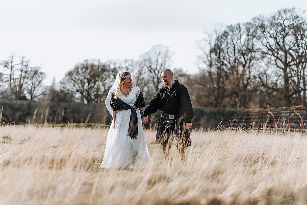 Couple walking through the grass in wedding dress and kilt in highlands