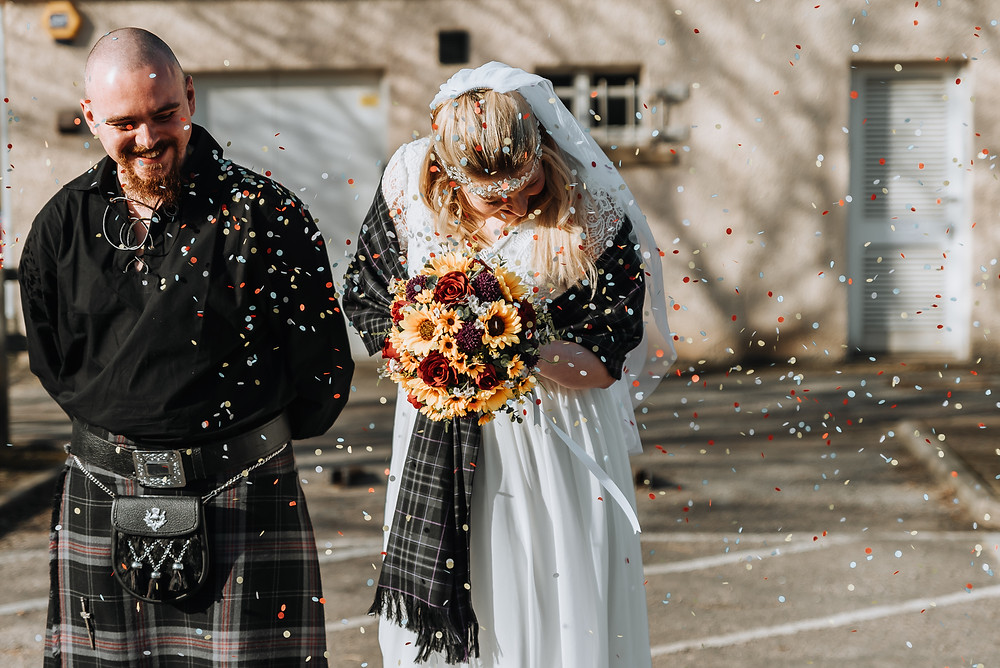 A bride and groom are covered in colourful confetti in a car park behind the registry office in Elgin, Moray