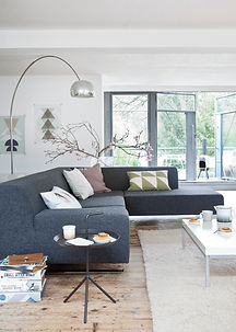 Interieur, woonkamer met hoekbank, houten vloer en booglamp