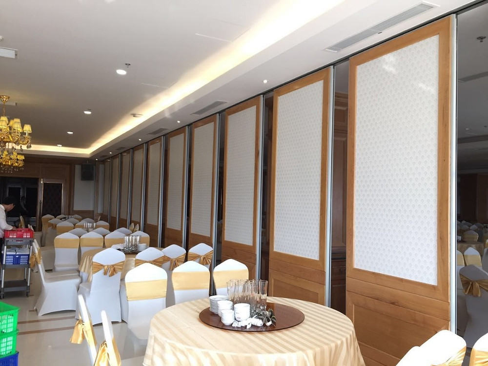 These are folding wall panels that are designed to slide along a connected ceiling track rail system. Each panel can slide by a single hanging wheel which can rotate 360 degrees or two hanging wheels that enables it to glide effortlessly. The panels are packed and stored remotely in its stacking area when not in use and spread out to make a temporary acoustic wall when extended.  The panels are furnished with mechanical top and base retractable seals which stretch in and out (when needed) to seal the boards in place and keep sound from travelling through or around the panels.