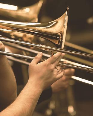 Mãos do homem que joga o trombone