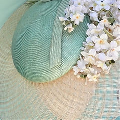Elegant wide brimmed hat with cluster of delicate silk flowers