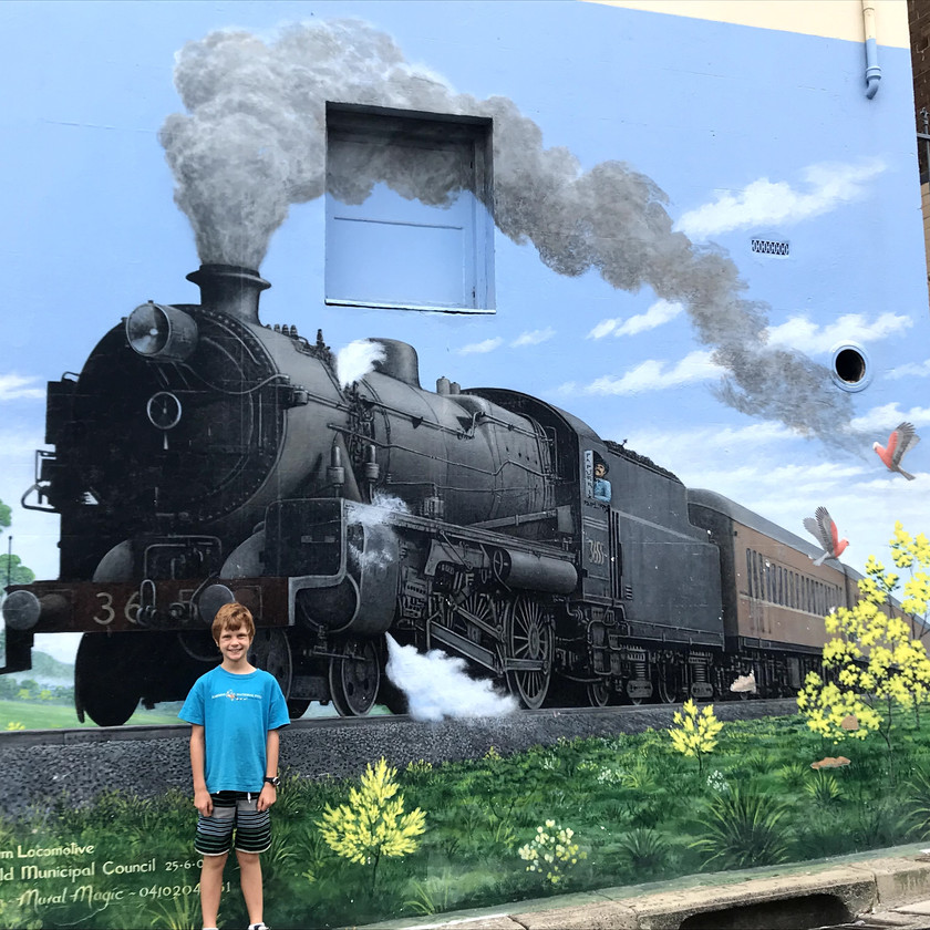 chase in front of steam train mural