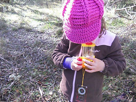 child outdoors with bug catcher
