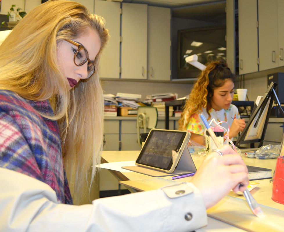 SIERRA BROSIUS worked on her panoramic art while Jessel Martinez, right, finished a portrait in art class at Woodford County High School. Beginning next school year, WCHS will implement an academy system that offers college and career pathways for all students. (Photo by Bob Vlach)