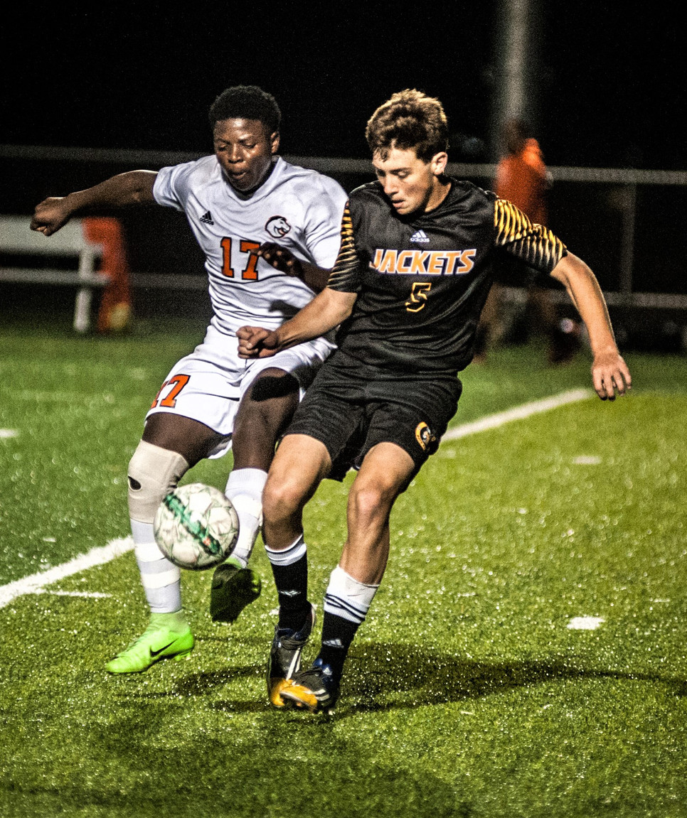 GAVIN NICHOLSON fights for a loose ball with Frederick Douglass player Innocent Lumona in the game at Frederick Douglass high school on Oct. 5. The Jackets won the game 5-1. (Photo by Bill Caine)
