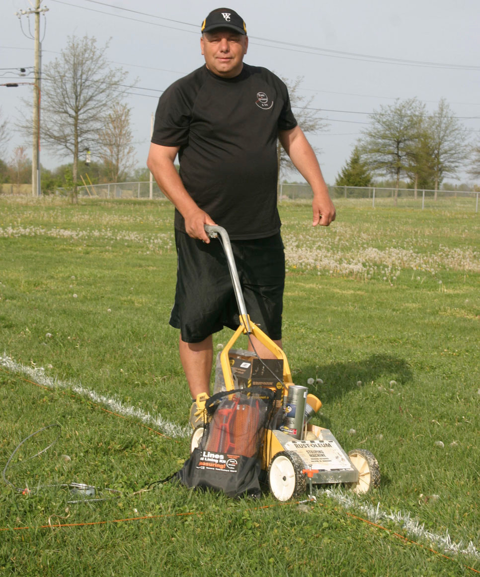 "WILLIAM ""DUSTY"" WETHINGTON, inventor of the Easy Crease and EC Lines field-striping systems, prepares to paint the field Tuesday morning before an afternoon lacrosse game. Wethington said he's sold more than 1,000 kits. (Photo by John McGary)"