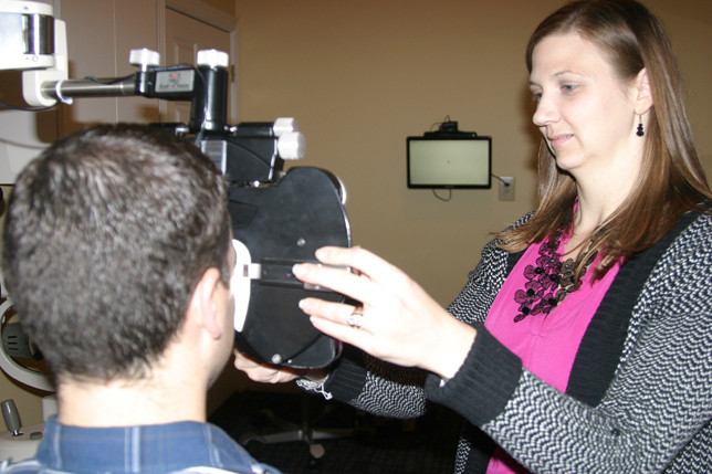 REBECCA SWARTZENTRUBER, with the help of her husband, Michael, to demonstrate one of the pieces of equipment at Family Eyecare Associates, a Crossfield Drive business that also operates the Children's Vision and Learning Center next door. The Swartzentrubers met at Centre College and have two young foster children. (Photo by John McGary)