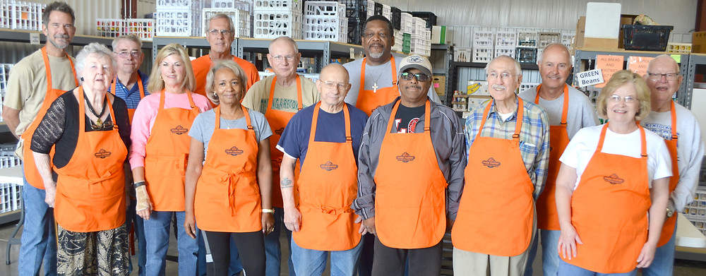 FOOD PANTRY VOLUNTEERS are wearing new aprons to serve hungry families in the community. From left, front, are Betty Dozier, Pam King, Doris Johnson, Ron Peters, Ralph Johnson, Jim Hughes and Sharon Hardin, director of the Food Pantry for Woodford County; back, Jeff Donoho, Bill Furlong, Bill Phelps, Jim Foster, Fred Gudger, John Thompson and Dick Brock. The aprons with the food pantry logo were donated by Troy Presbyterian Church. (Photo by Bob Vlach)