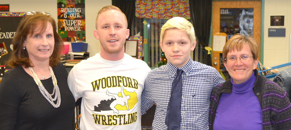 CHASE YOST, an eighth-grader at Woodford County Middle School, was honored by the Woodford County Board of Education on Monday for winning an individual state title at the KHSSA State Wrestling Championships on Feb. 19 and 20. Chase and his Woodford County High School teammates finished second in the team standings. From left are board member Margie Cleveland, WCHS wrestling Coach Rusty Parks, Chase, and board member Karen Brock. (Photo by Bob Vlach)
