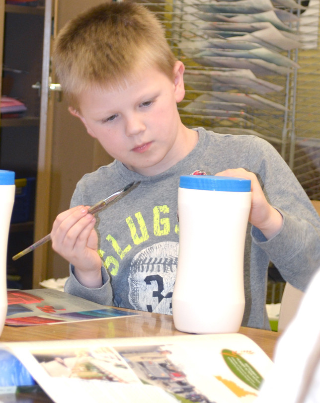 BRAYDEN CASH, a second-grader at Northside Elementary, painted glue on a container for a papier maché project that combines the colorful artwork of several students to create a sculpture. Student artwork will be exhibited at the Francisco Farm's Art Fair on May 19 and 20. (Photo by Bob Vlach)