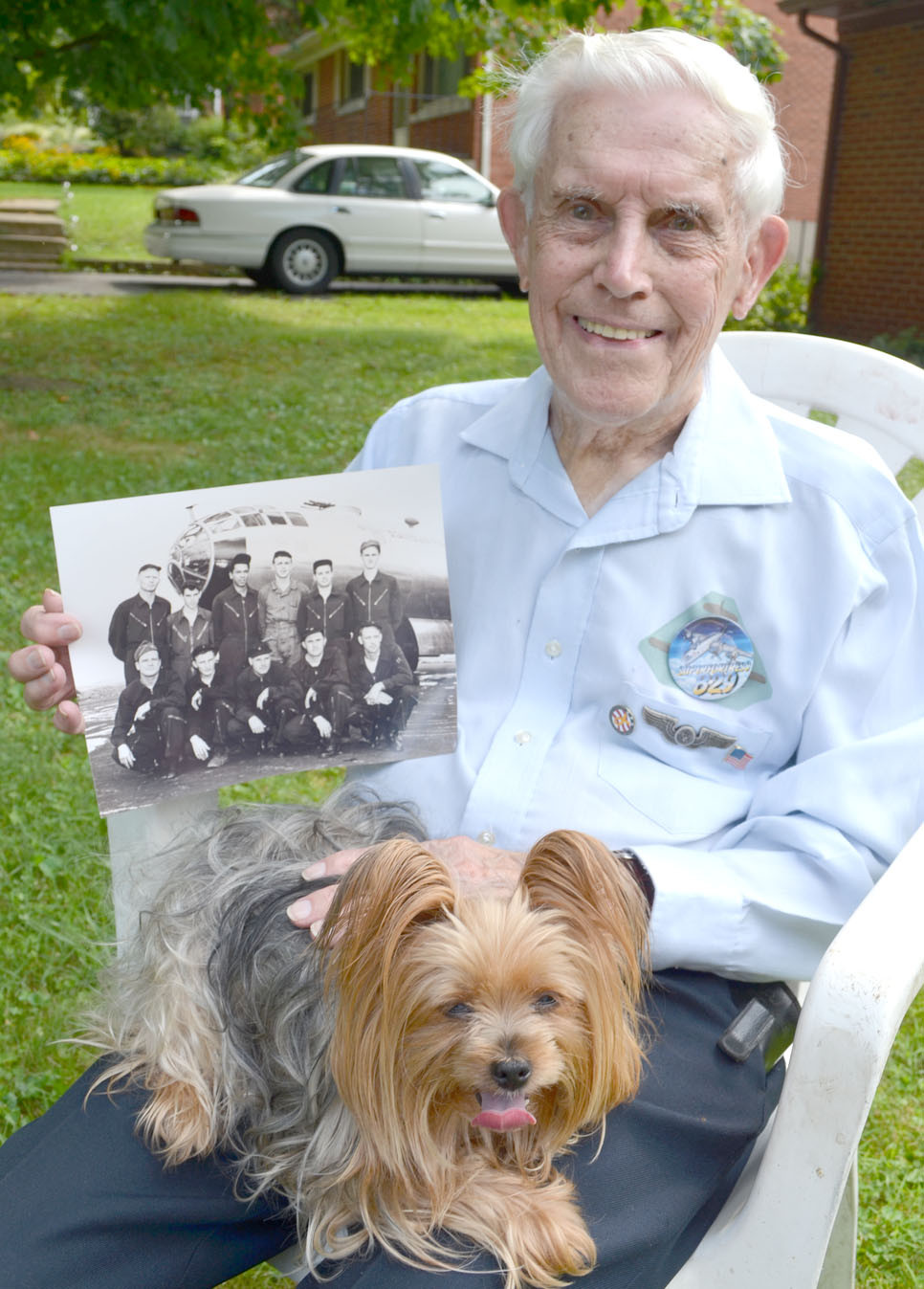 LONNIE ADKINS JR., a Midway resident, is pictured with a photo of his 11-man B-29 crew and holding his teacup yorkie, Zoey. (Photo by Bob Vlach)