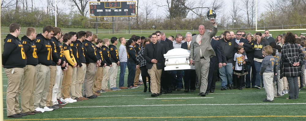 THE COFFIN CARRYING the body of Logan James Dean Tipton was carried off the field at Community Stadium Friday after an emotional, hour-long service for the six-year-old. (Photo by John McGary)