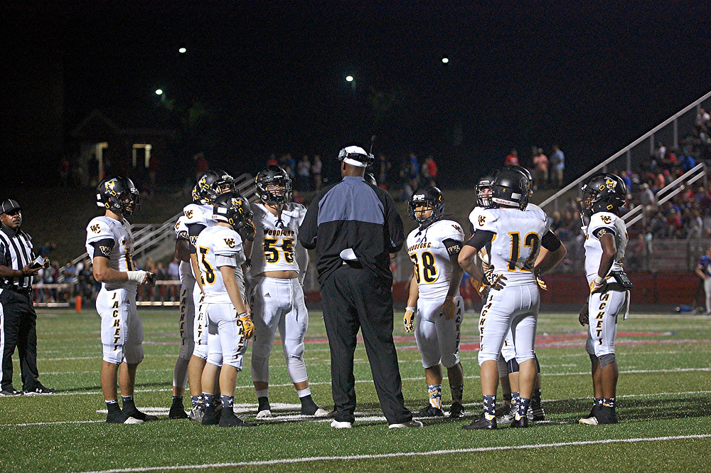 HEAD COACH Dennis Johnson, dark jacket, tries to rally his team during the Woodford County High School football team's game at Madison Central on Friday, Sept. 23. However, at the final buzzer, the Yellow Jackets lost, 42-0. (Photo by Rick Capone)