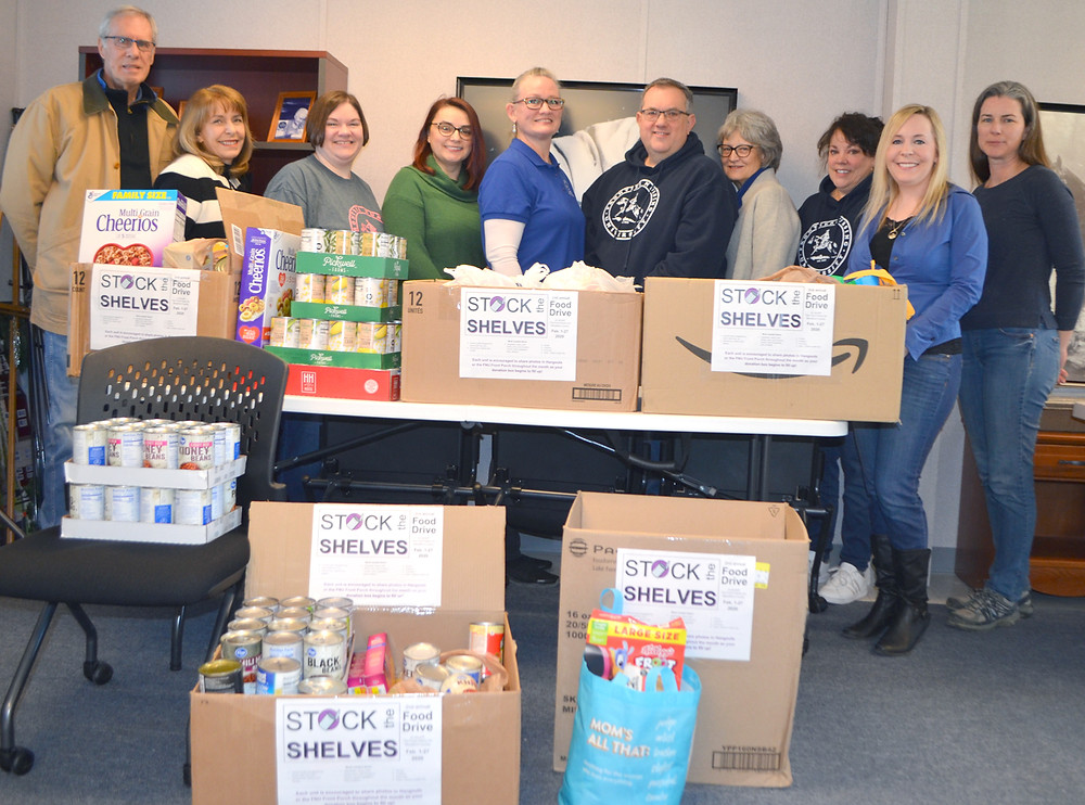 THE FOOD PANTRY FOR WOODFORD COUNTY accepted a donation of 374 pounds of nonperishable food items from Frontier Nursing University employees last Friday, Feb. 28. From left are food pantry board President Bill Phelps, FNU President Susan Stone, with employees Jennifer Howard, Jelena Djuricic, Sharon Tankersley, James Kelsey, Linda Barnes, Christi Ohr, Brittney Kinison and Shelley Aldridge. (Photo by Bob Vlach)